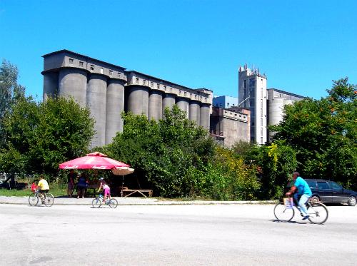 Велосипедисты на фоне хлебзавода